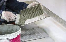 维修服务 放置地板陶瓷砖 人在手套的` s手与小铲,在陶瓷地垫的被涂的水泥灰浆 免版税图库摄影