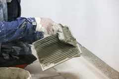 维修服务 放置地板陶瓷砖 人在手套的` s手与小铲,在陶瓷地垫的被涂的水泥灰浆 库存图片