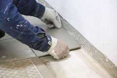 维修服务 放置地板陶瓷砖 人在手套的` s手与小铲,在陶瓷地垫的被涂的水泥灰浆 免版税库存照片