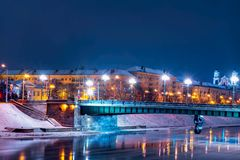 维尔纽斯市在冬天在晚上,河涅里斯河,对桥梁的看法有许多光和维尔纽斯老镇的,多雪的平衡的维尔纽斯 2018-01- 库存照片