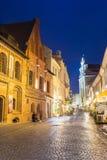 维尔纽斯立陶宛 古老大厦有启发性门面在老镇著名Pilies街上的在夜,普遍 免版税库存图片
