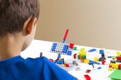维尔纽斯,立陶宛- 2017年10月15日:使用与lego建筑玩具块的男孩 免版税库存照片