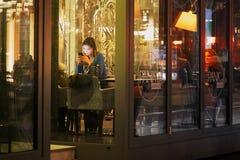 维尔纽斯,立陶宛- 2017年11月5日:咖啡馆的一个女孩坐与电话 免版税图库摄影