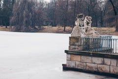 维斯瓦河的讽喻由Ludwik Kauffman的有华沙皇家浴的冻湖的在冬天停放 免版税库存照片