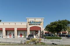 维生素商店零售店的前面在一个晴天 维生素商店商店的门面有一个停车场的在前面 免版税库存照片