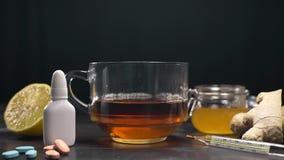 维生素红茶用姜、柠檬和蜂蜜在与药片的桌和温度计,自然治疗上站立反对 影视素材