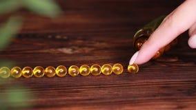 维生素补充药片Ω 3 在木桌上的鱼肝油医学 鱼油胶囊 股票视频