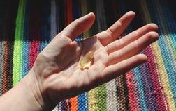 维生素D或Ω 3个胶囊 维生素胶凝体在手中反对窗口 维生素D缺乏的概念在身体的 库存图片