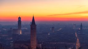 维罗纳、托尔兰贝蒂和圣诞老人阿纳斯塔西娅老镇美好的全景日落视图用平衡雾盖的钟楼 免版税库存图片