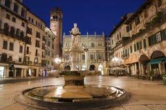 维罗纳-在广场Erbe的喷泉在黄昏和Porta Leona和Palazzo Maffe 免版税库存照片