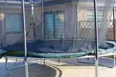 绷床 跳跃的绷床 有安全网的室外绷床 免版税库存图片