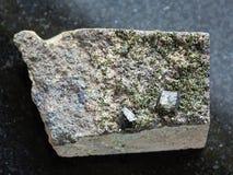 绿帘石未加工的绿色水晶在岩石的在黑暗 免版税库存照片