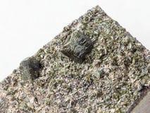 绿帘石水晶在岩石关闭的在白色 免版税库存照片