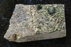 绿帘石粗砺的水晶在岩石的在黑暗 图库摄影