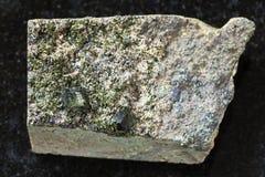 绿帘石粗砺的绿色水晶在岩石的在黑暗 免版税库存照片