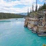 绿松石河流动在美丽如画的岩石附近的阿萨巴斯卡 免版税库存图片