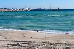 绿松石海、白色游艇、灯塔和脚印在沙子在一好日子 图库摄影