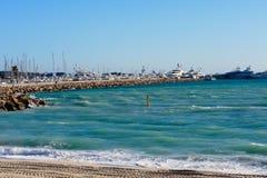 绿松石海、白色游艇、灯塔和脚印在沙子在一好日子 戛纳,法国 免版税图库摄影