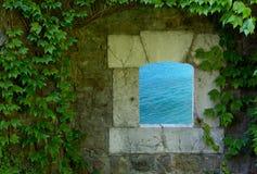 绿松石海通过一个老外部窗口 免版税库存照片