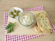 绿橄榄和乳脂干酪面包传播  库存照片