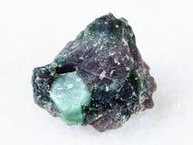 绿玉宝石粗砺的水晶在岩石的在白色 免版税库存照片