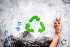 绿皮书回收在废聚乙烯袋中的标志和在灰色石背景顶视图的塑料瓶复制 免版税库存图片