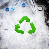 绿皮书回收在废聚乙烯袋中的标志和在灰色石背景顶视图的塑料瓶复制 免版税库存照片