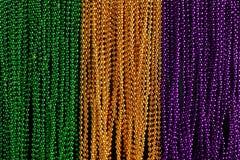 绿色、金子和紫色狂欢节小珠 免版税库存图片