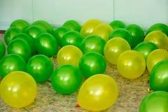 绿色两个的颜色和在地板上的黄色谎言气球  图库摄影