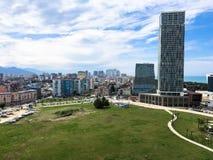 绿色公园在一个现代大城市,有高玻璃房子的,大厦,反对山的天空蔚蓝的摩天大楼特大的城市 免版税库存照片