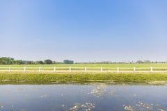 绿色农业领域正面图与白色篱芭、湖和天空的 库存照片