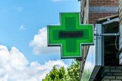 绿色发怒药房标志或标志在大厦门面视图从街道 免版税库存照片