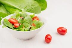 绿色叶子,在白色木板,特写镜头,拷贝空间的切片红色西红柿水多的新鲜的沙拉  免版税库存照片
