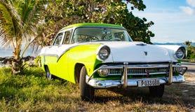 绿色和白色福特Fairlane在海滩停放了 图库摄影