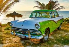 绿色和白色福特Fairlane在海滩停放了 库存图片