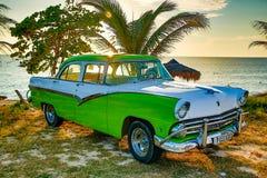 绿色和白色福特Fairlane在海滩停放了 免版税图库摄影