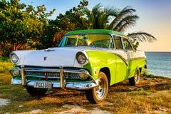 绿色和白色福特Fairlane在海滩停放了 免版税库存图片