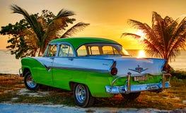 绿色和白色福特Fairlane在海滩停放了 免版税库存照片