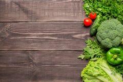 绿色和红色新鲜蔬菜框架在木背景,顶视图的 库存照片