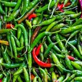 绿色和红色chillis堆在零售菜超级市场f上 免版税库存图片