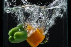 绿色和黄色喇叭花胡椒在水中在黑背景飞溅 免版税库存图片