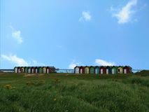 绿色围场和小屋与蓝天 免版税库存照片