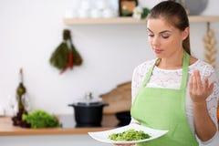 绿色围裙的少妇在厨房里烹调 主妇提供新鲜的沙拉 免版税图库摄影