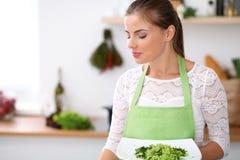 绿色围裙的少妇在厨房里烹调 主妇提供新鲜的沙拉 免版税库存图片