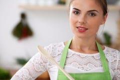 绿色围裙的少妇在厨房里烹调 考虑菜单的主妇,当拿着一把木匙子时 库存照片