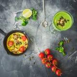 绿色圆滑的人用菠菜、素食煎蛋卷、蕃茄和南瓜籽 平的位置,顶视图 免版税库存照片