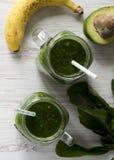 绿色圆滑的人用鲕梨、菠菜和香蕉在玻璃瓶子在白色木表面,顶视图 r 库存图片