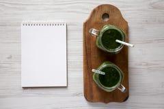 绿色圆滑的人用鲕梨、菠菜和香蕉在玻璃瓶子,空白的笔记薄在白色木表面,顶上的看法 r 库存照片