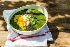 绿色圆滑的人碗用香蕉、菠菜、chia种子和桔子 库存照片