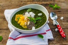 绿色圆滑的人碗用香蕉、菠菜、chia种子和桔子 图库摄影